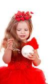 Niña con vestido rojo con bola de navidad. — Foto de Stock