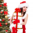 Christmas girl in santa hat and fir tree with red gift box. - Stock Photo