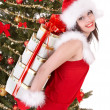 Christmas girl in santa hat and fir tree with red gift box. - 图库照片