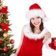 Christmas girl in santa hat giving gift box. — Stock Photo #7610228