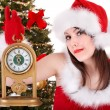 Girl in santa hat holding clock. - Stock Photo