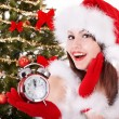Christmas girl in santa hat holding clock. - Stock Photo