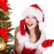 Girl in santa hat call mobile phone by christmas tree. — Stock Photo #7610250