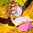 Kid in autumn orange leaves with laptop. — Stock Photo