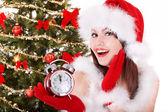рождество девушка в шляпе санта холдинг будильник. — Стоковое фото