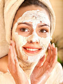 Young woman having clay body mask. — Stock Photo