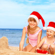 Children in santa hat playing on beach. — Stock Photo #7840476