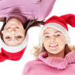Girls in santa hat lying head next to head. — Stok fotoğraf