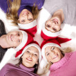 Group in santa hat lying head next to head. — Zdjęcie stockowe