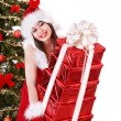 Royalty-Free Stock Photo: Girl in santa hat giving stack red gift box.