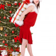 Christmas girl in santa hat holding red gift box. — Stock Photo #7843752