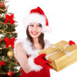 Girl in santa hat giving gift box. — Stock Photo