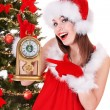 Christmas girl in santa hat holding clock. - 图库照片