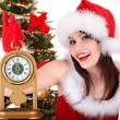 Christmas girl in santa hat and fir tree with alarm clock. - Foto Stock