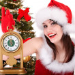 Christmas girl in santa hat and fir tree with alarm clock. - Stock fotografie