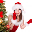 Girl in santa hat call mobile phone by christmas tree. - Foto Stock