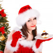 Girl in santa hat eat cake by christmas tree. — Stock Photo #7843789