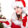 Christmas girl in santa hat and cake on plate. — Stock Photo #7843799