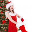 Girl in santa hat holding christmas stocking and gift box. — Stock Photo #7843800