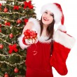 Girl in santa hat holding christmas socks and gift box. — Stock Photo #7843804