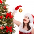 Girl in santa hat decorete christmas tree. - Foto Stock