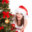 Girl in santa hat by christmas tree. — Stock Photo #7843832