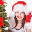 Girl in santa hat  listen near  christmas tree. — Stock Photo
