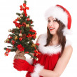 Girl in santa hat holding christmas tree. - Foto de Stock