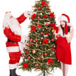 Girl and santa clause by christmas tree. — Photo