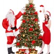 Royalty-Free Stock Photo: Santa claus and girl by christmas tree .