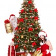 Stock Photo: Santa claus and girl by christmas tree .