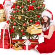 Royalty-Free Stock Photo: Santa claus and girl by christmas tree and gift box.