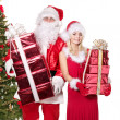 Santa claus and girl holding gift box by christmas tree.. — Stockfoto #7846551
