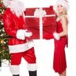 Santa claus and girl holding gift box. — Stock Photo