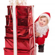 Child in santa hat by stack gift box. — Stock Photo #7846574