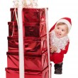 Child in santa hat by stack gift box. — Stock Photo