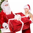 Santa claus and girl holding gift box by christmas tree.. — Stock Photo #7846698