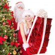 Santa claus and girl holding gift box by christmas tree.. — Stockfoto #7846709