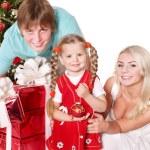 Happy family in santa hat holding gift box. — Stock Photo