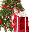 Child giving gift box by christmas tree. — Stock Photo #7846775