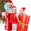Happy family in santa hat holding gift box. — Stock Photo #7846781