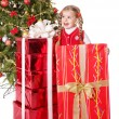 Child holding gift box by christmas tree. — Stock Photo #7846790