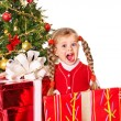 Child giving gift box by christmas tree. — Stock Photo