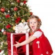 Child holding gift box by christmas tree. — Stock Photo