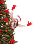Christmas girl in santa hat near tree hand up. — Stock Photo