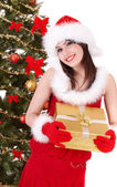 Christmas girl in santa hat and fir tree with gold gift box. — Stock Photo