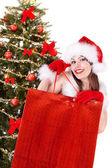 Christmas girl in santa hat giving gift box. — Stock Photo