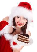 Christmas girl in santa hat eat cake on plate. — Stock Photo