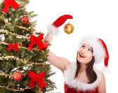 Girl in santa hat decorete christmas tree. — Stock Photo