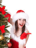 Christmas girl in santa hat point, fir tree. — Stock Photo
